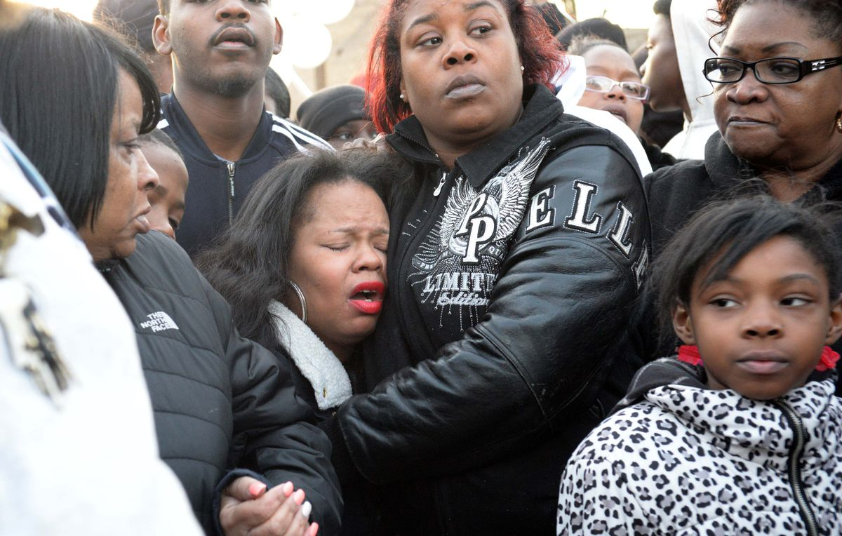 Tambrasha Hudson (center, eyes closed), the mother of 16-year-old Pierre Loury, attends a vigil the day after her son was shot and killed.