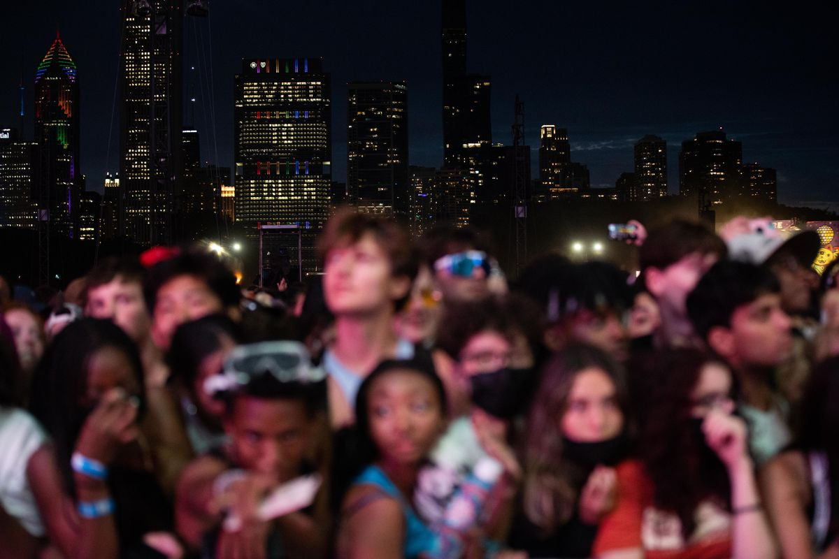 """Lights that spell """"Vacc to Lolla"""" is seen on a building as festival goers wait for Tyler."""
