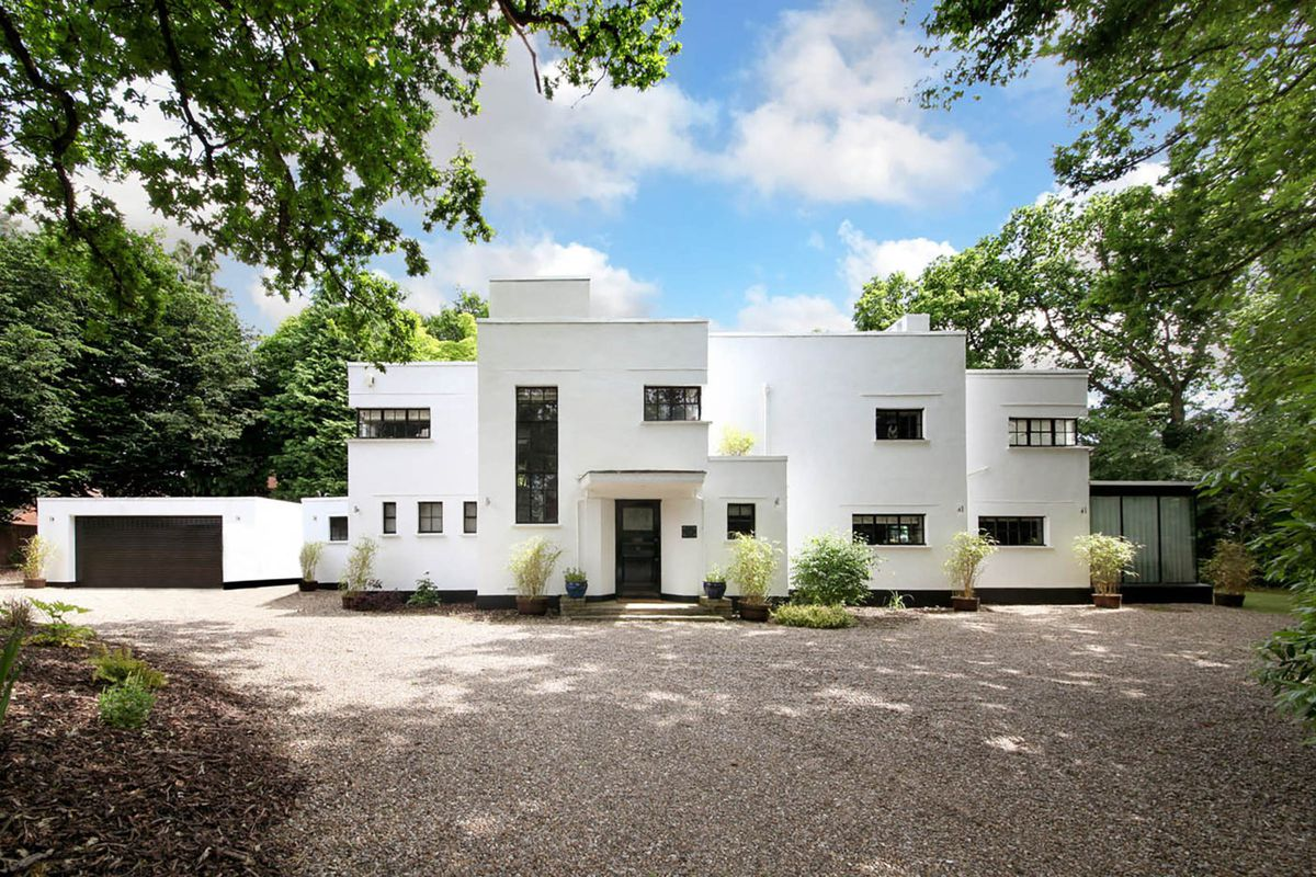 Asymmetric two-story home comprising cubic volumes and small windows, white walls.