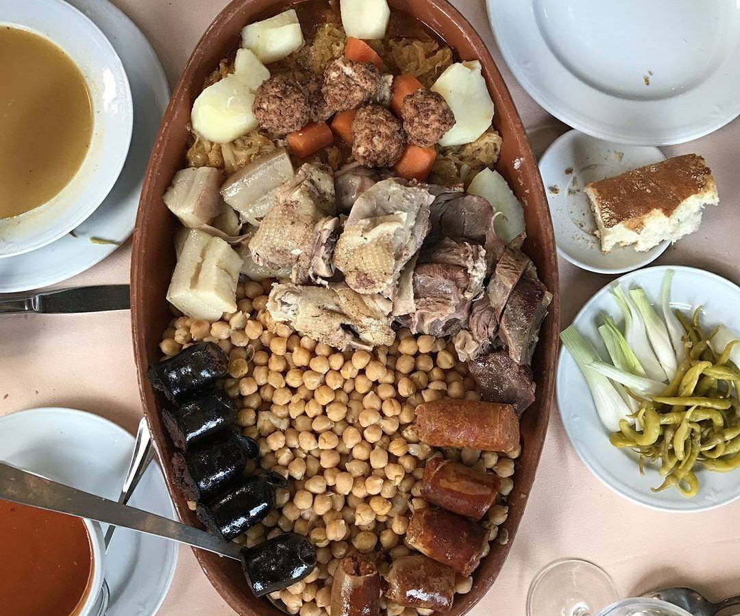 A large tray with different cuts of meat and chickpeas in the center of several other half-eaten dishes, including vegetables, breads, and soups.