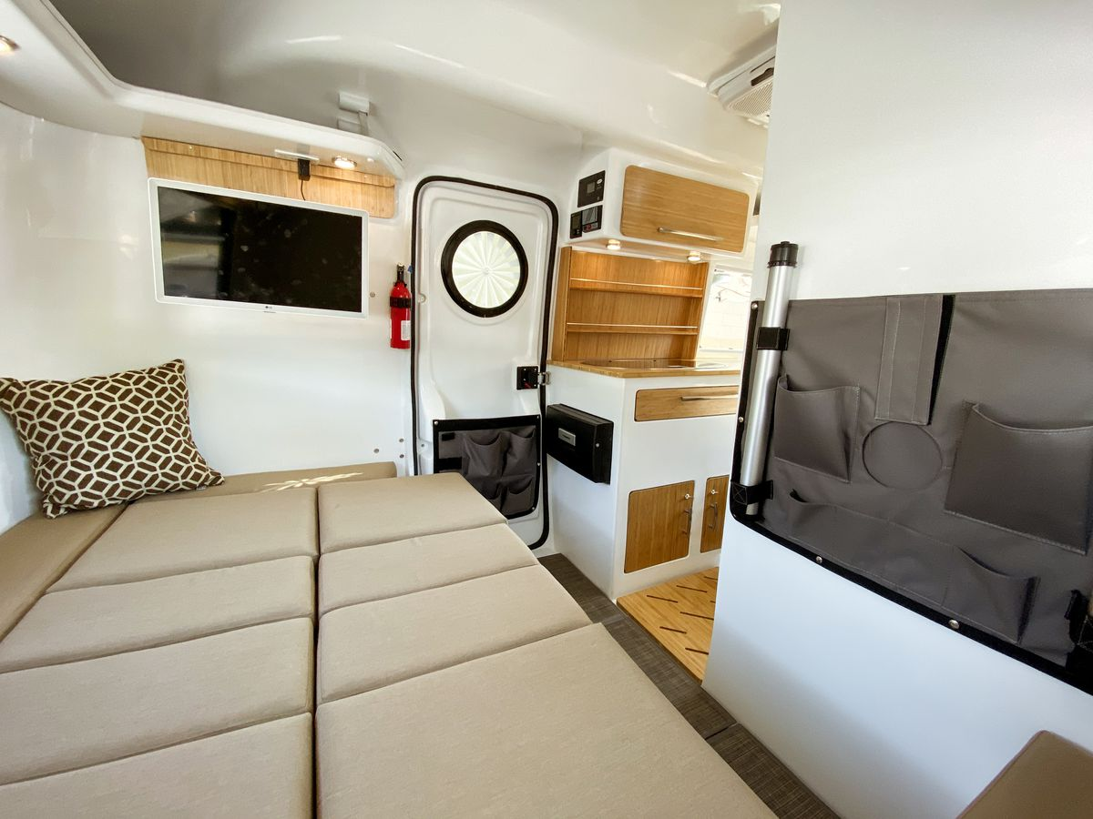 The interior of a travel trailer features a bed made up of beige cubes with a view into the kitchenette.