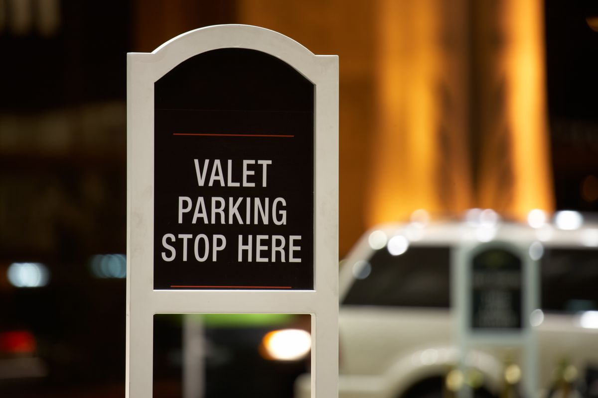 A sign that says valet parking stop here