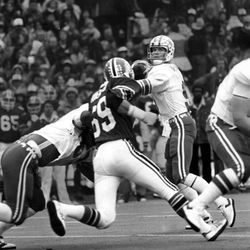 BYU's Jim McMahon is ready to fire a pass to one of his many receivers as a University of Utah player tries to maneuver past a defender for a sack.