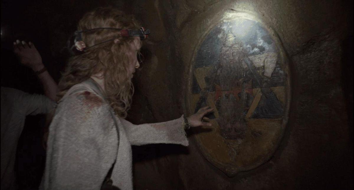 Perdita Weeksplaces her hand against an underground mural inAs Above, So Below (2014)