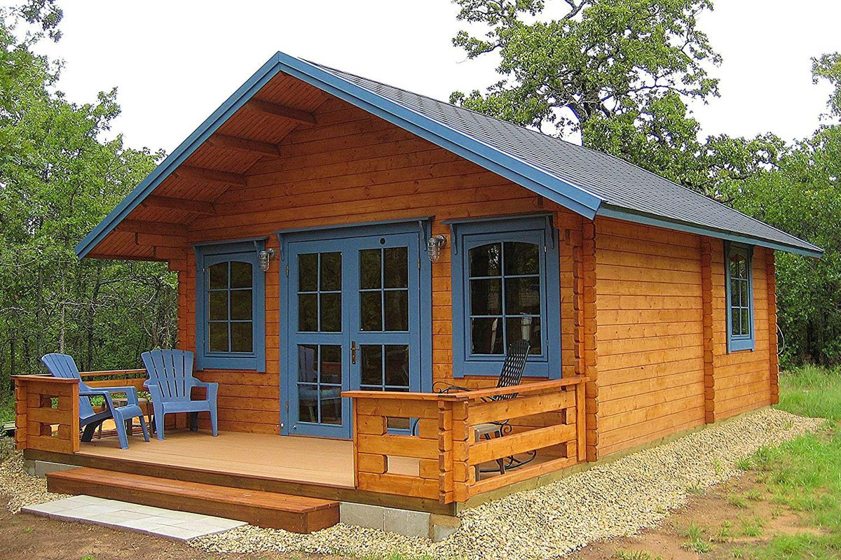 There is a wooden cabin with front porch and blue trimmed windows sitting in a forest.