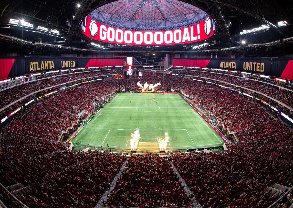A large sports stadium with a field in the center. Above the stadium is a marquee with the word: Goal.