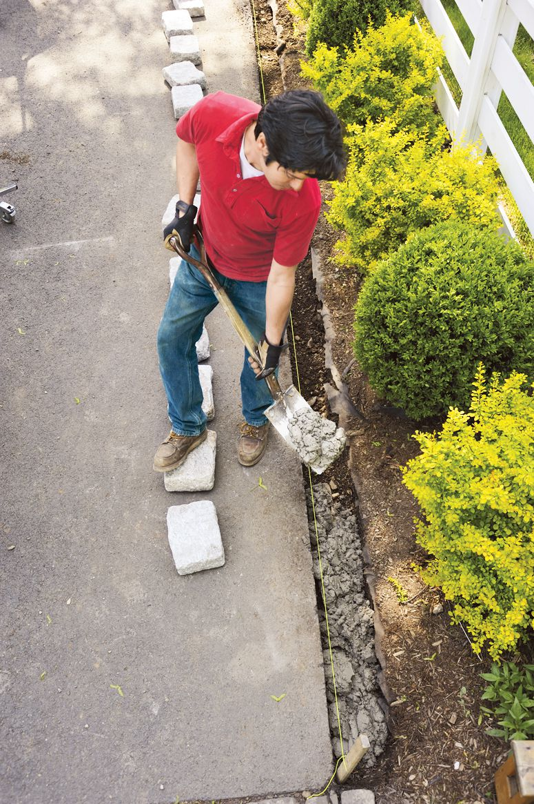 Man Adds Concrete To Trench To Prepare For Belgian Blocks