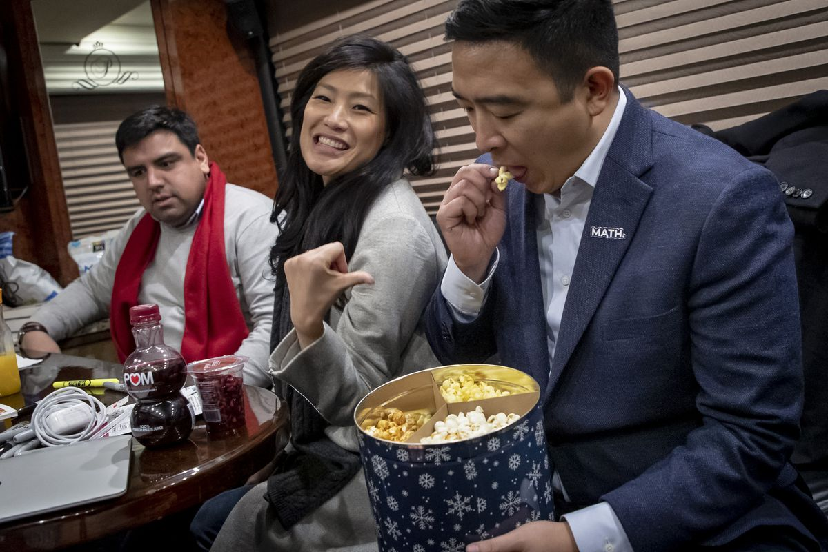 Man sitting eats from a tin of three-flavored popcorn while woman sitting next to him gestures toward him.
