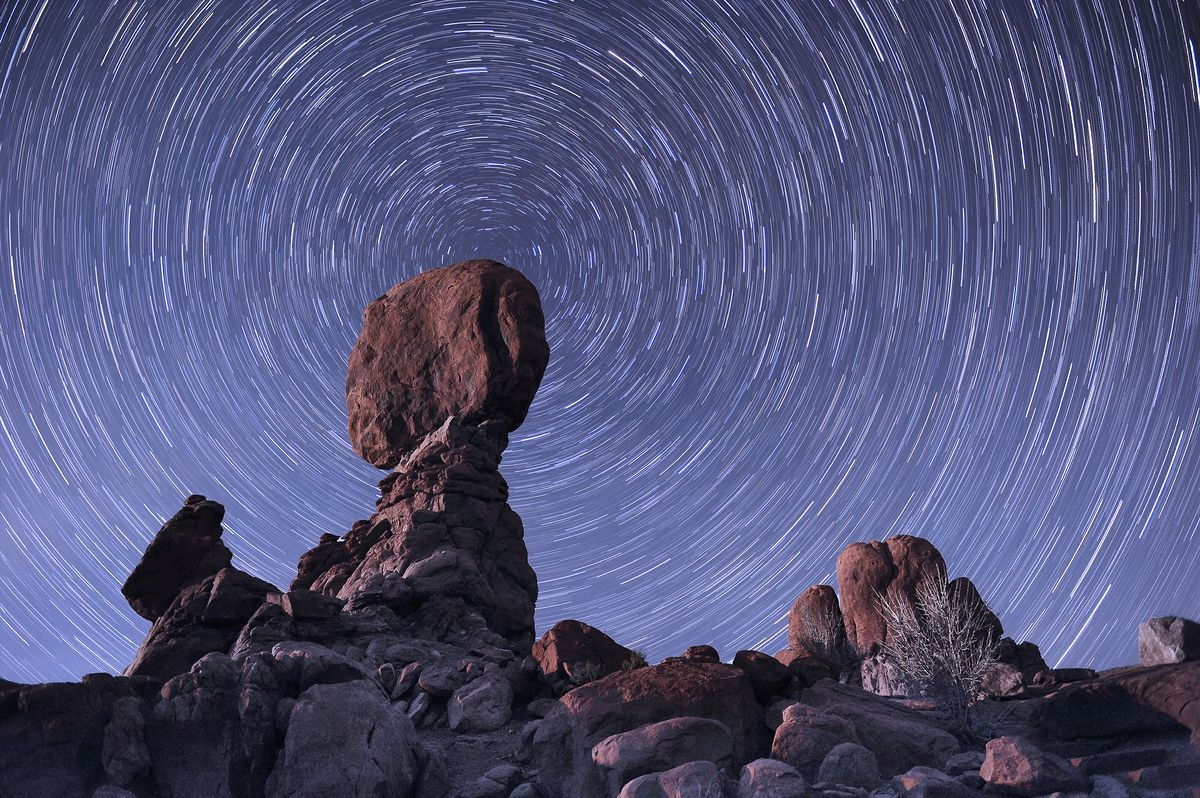 The stars trail around the northern pole star with the famous Balance Rock in the foreground, Arches National Park, Moab, Utah.