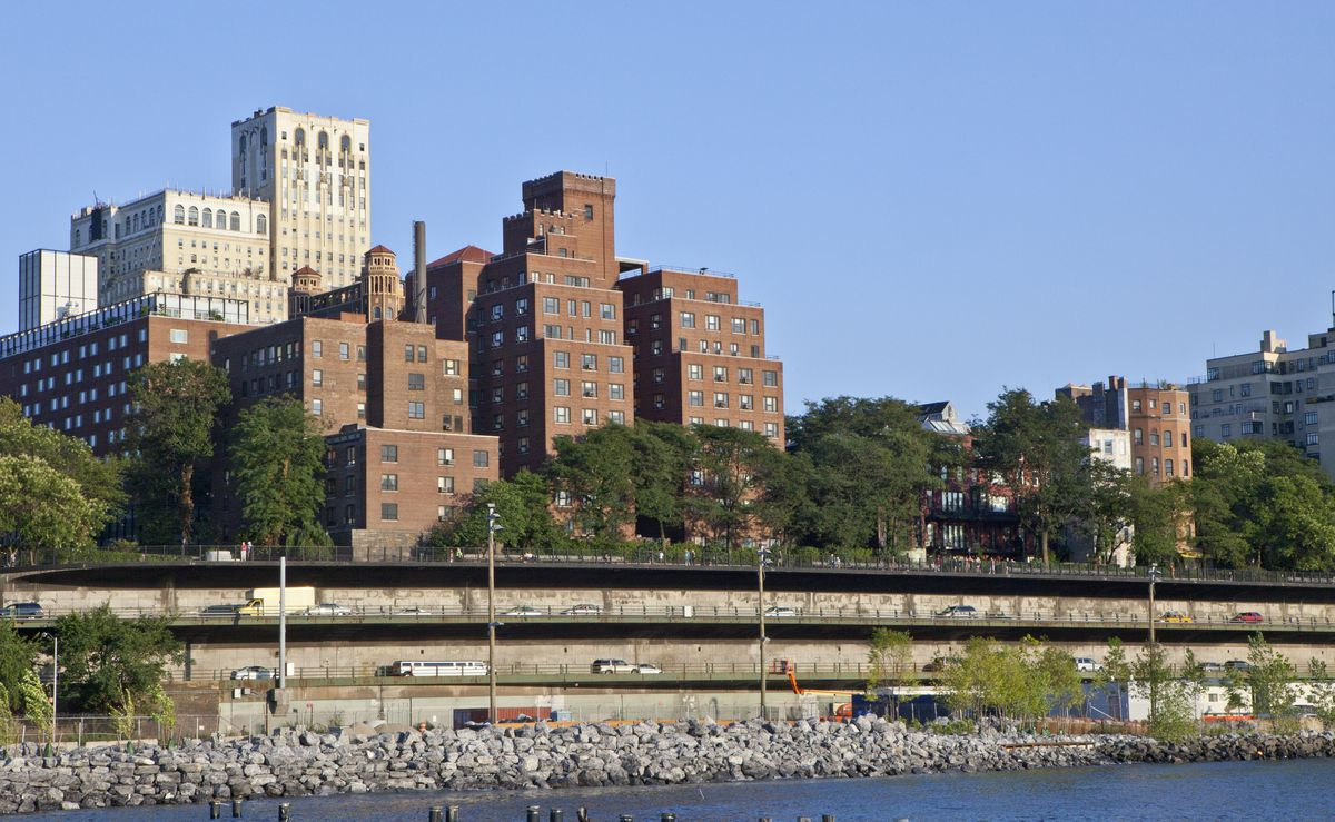 A view of the triple-cantilever section of the Brooklyn Queens Express from west. The view shows three tiers of traffic with the Brooklyn Heights Promenade above and apartment buildings.