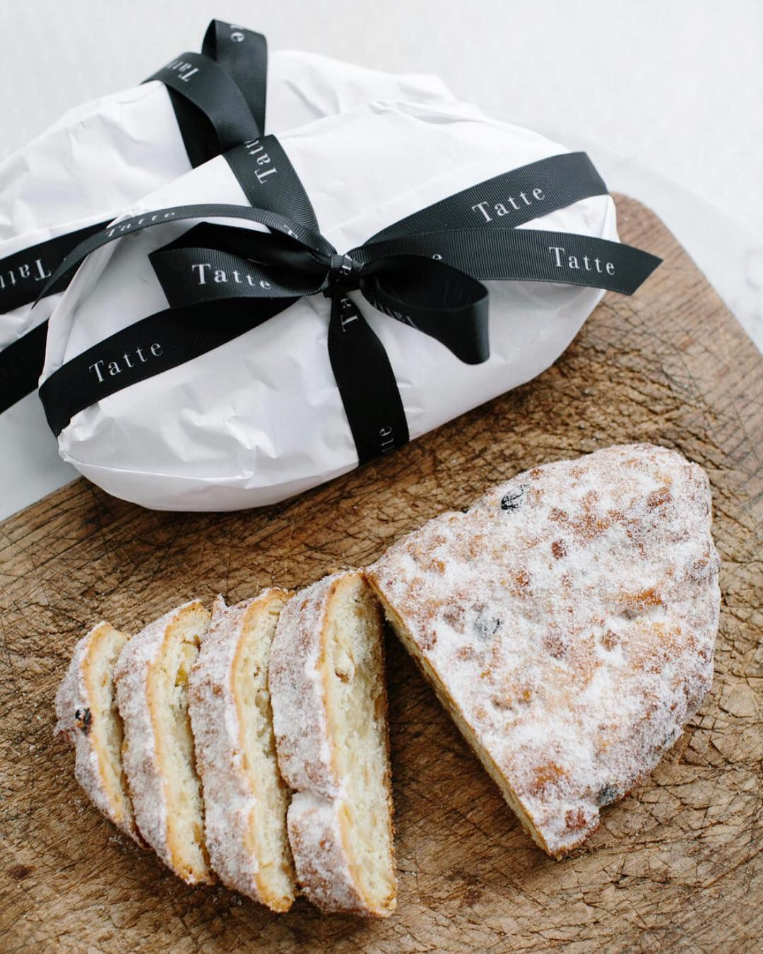 Tatte's stollen with fruit, nuts, and spices, dipped in butter and coated with powdered sugar