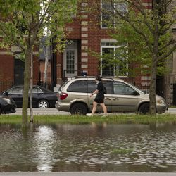 A woman walks past a flooded field at Humboldt Park, Monday, May 18, 2020. Much of the Chicago area experienced flooding after rain showers over the weekend.