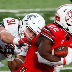 Utah Utes running back Ty Jordan (22) carries the ball against Washington State Cougars defensive back Hunter Escorcia (31) during an NCAA football game at Rice-Eccles Stadium in Salt Lake City on Saturday, Dec. 19, 2020.