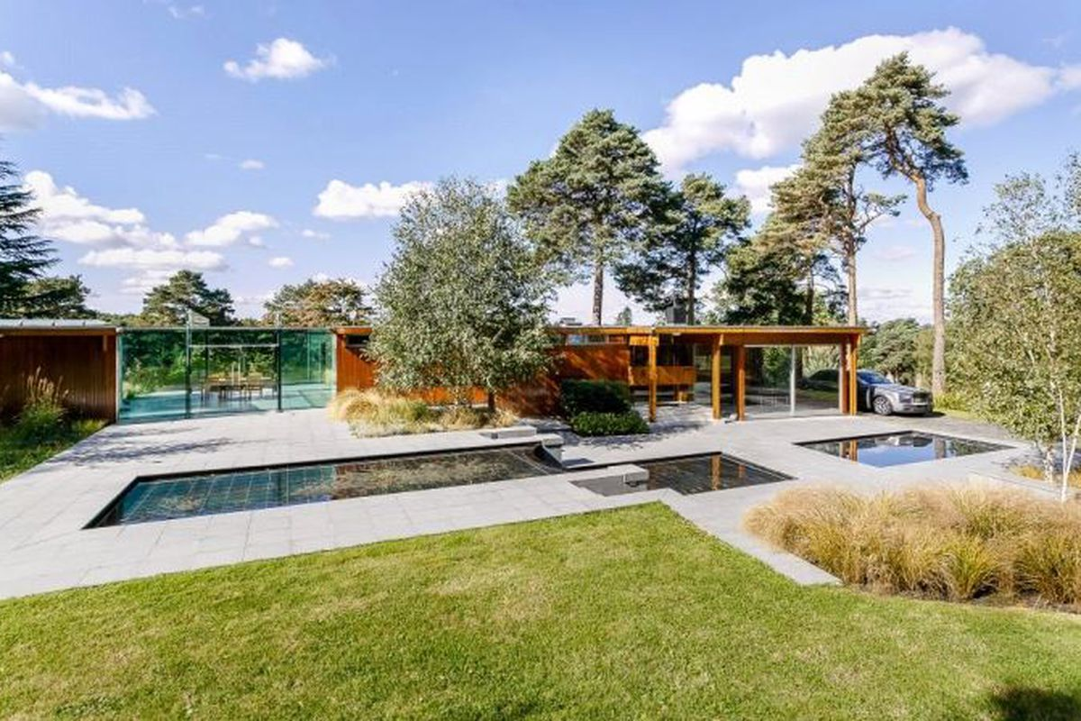 Flat-roofed post-and-beam modern home clad in timber and glass, with a terraced fountain in the front.
