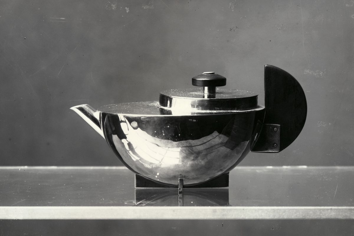 Black and white photo of a steel teapot, which is very curvy and circular.