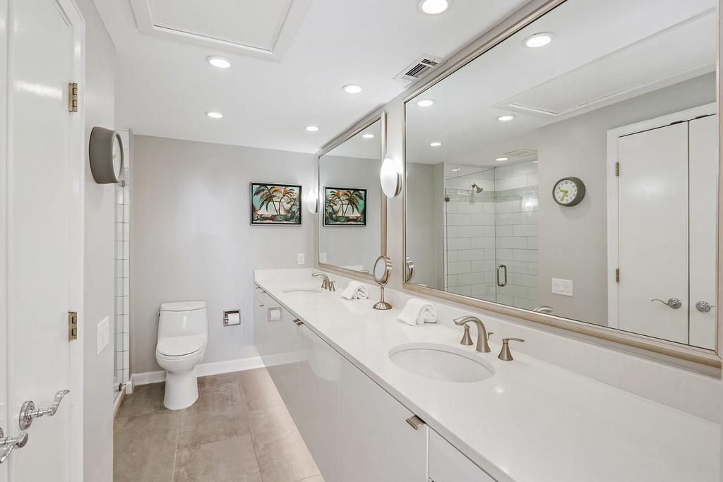 A huge white bathroom with two sinks.