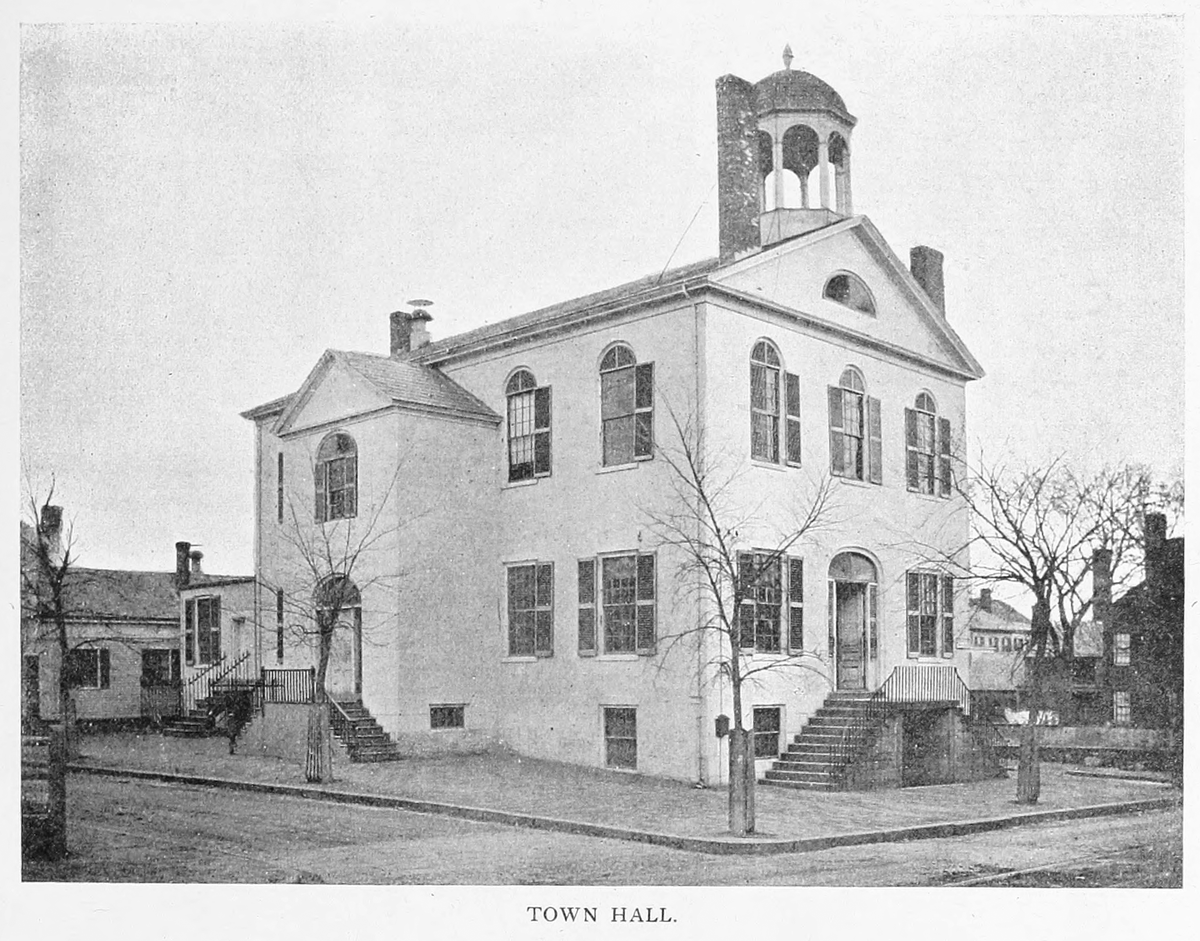 A historic photo of a white building with a bell tower on its roof.
