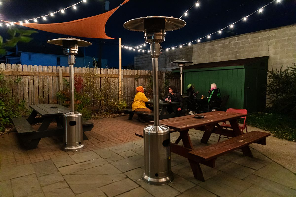 Customers sit at a picnic table bundled up on the patio at Bumbo's in Hamtramck surrounded by heaters at night.