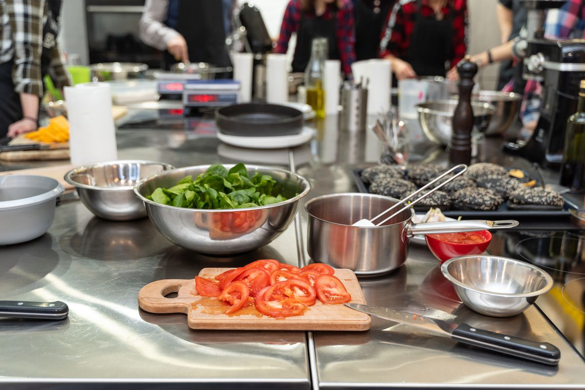 Sliced tomatoes and a bowl of lettuce sit on a counter in a culinary school kitchen.