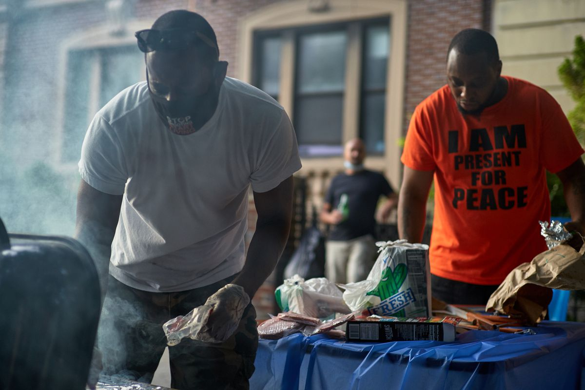 Block association president Mike Jones, right, helps make food during a street party on their stretch of St. John's Place in Prospect Heights, Brooklyn, Aug. 8, 2020.