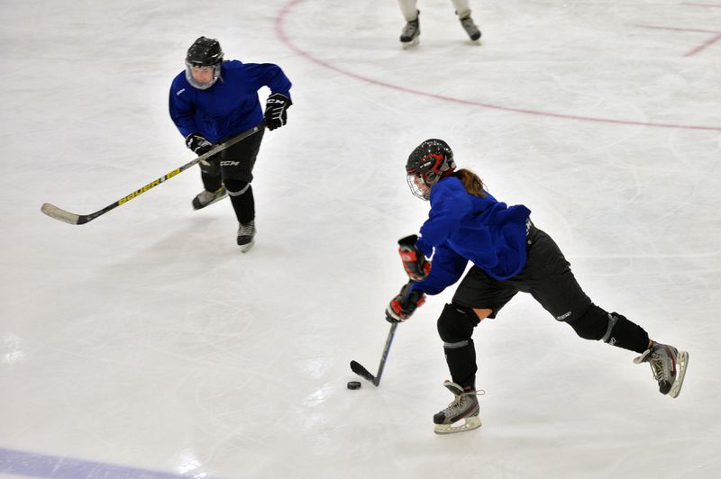 Rachel Arias (left) and Jessica Dare (right) of the Chicago North Stars, an elite women's hockey team, during practice at the Johnny's IceHouse West.