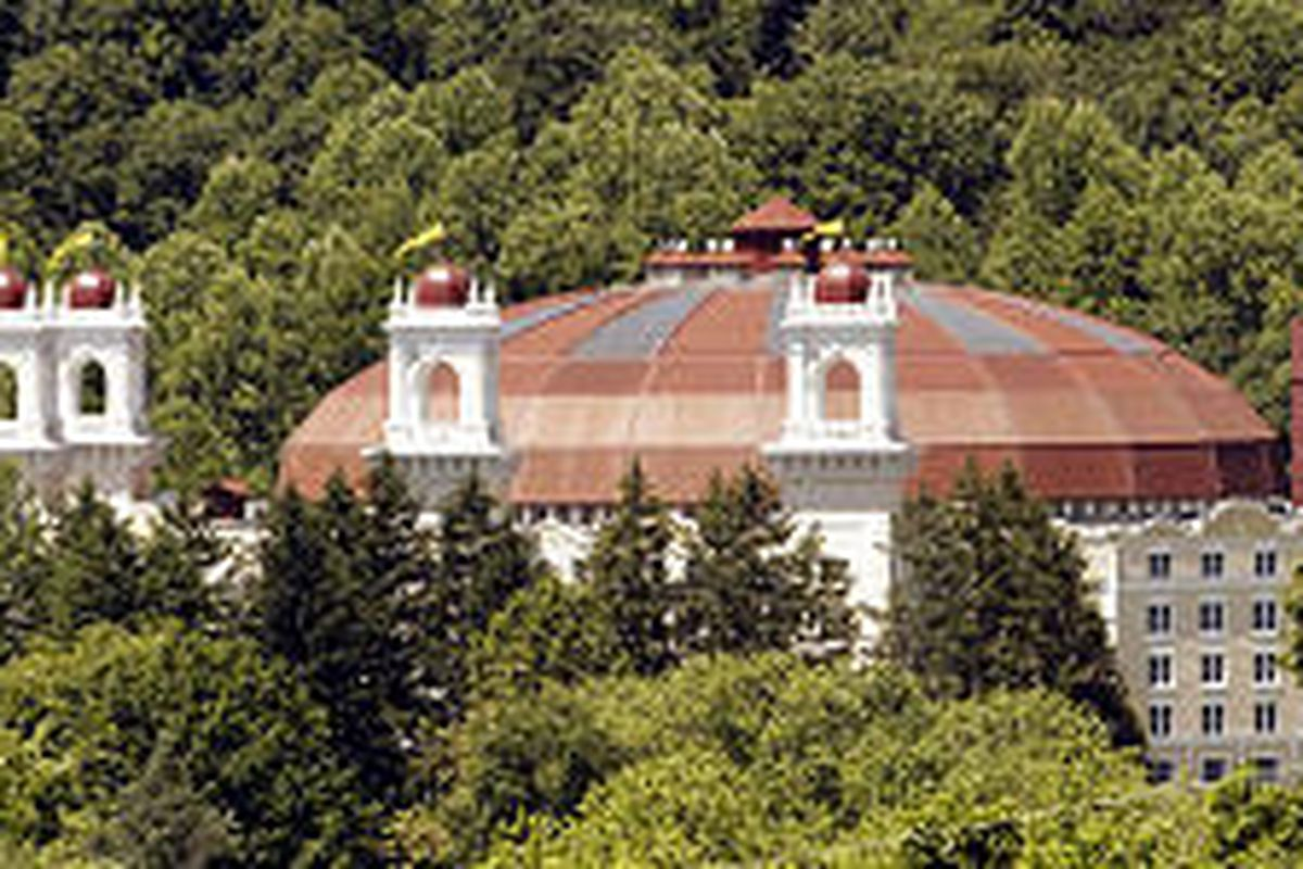 The glass-and-steel domed atrium of the century-old West Baden Springs Hotel rises above the trees in the town of West Baden, Ind.