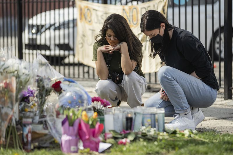Little Village residents Victoria Ramon-Fox (left) and Haley Scott light a candle at a memorial for Adam Toledo on Friday in the 2300 block of South Sawyer Avenue.