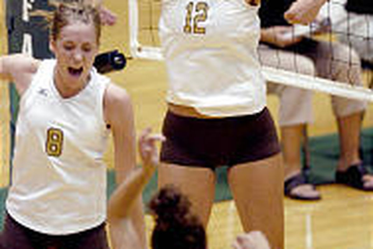 Davis' Kayla Walker (12) celebrates with teammates Tara Anderson (8) and Lindsey Scott (5) during their straight-set win over Clearfield.