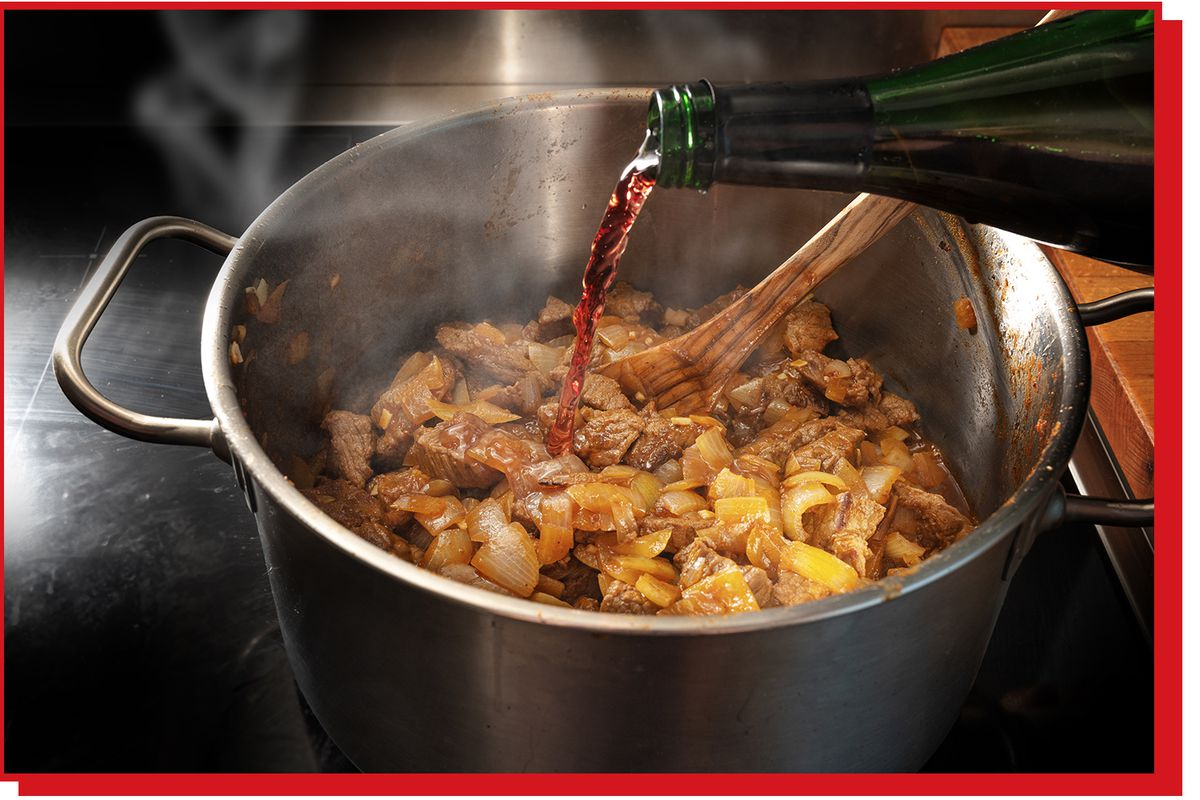 Bottle of red wine being poured into a pot simmering on the stove.