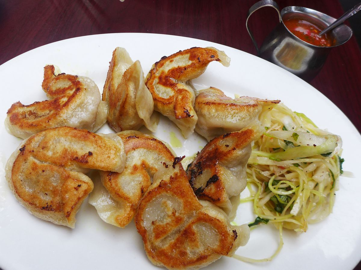 A plate of dumplings seared on one side with hot sauce on the side.