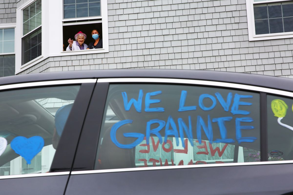 """A drive-by birthday party, with a car decorated with lettering: """"We love you Grannie."""""""