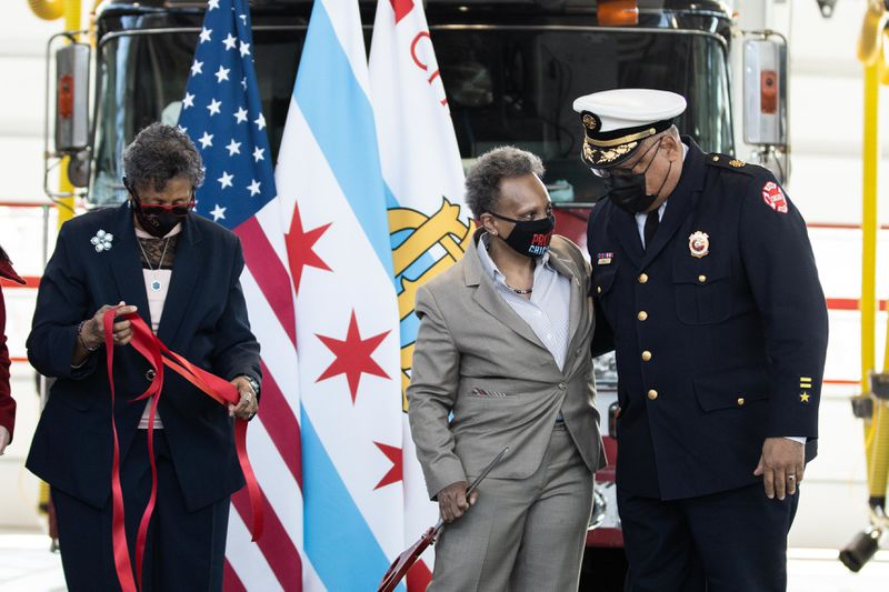 Chicago Mayor Lori Lightfoot speaks to retired Chicago Fire Department Commissioner Richard Ford while Ald. Carrie Austin (34th) holds a ribbon during the opening ceremony of Engine Company 115's new firehouse at 1024 W. 119th St. in the West Pullman neighborhood, Wednesday morning, March 31, 2021.