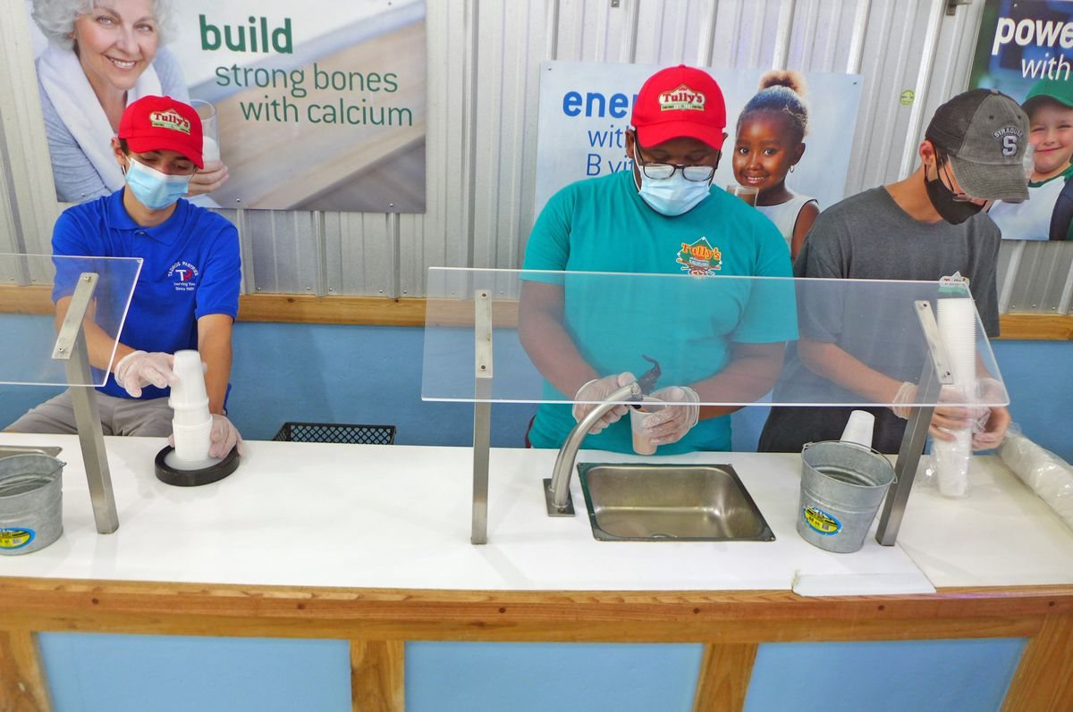 Three employees behind a counter with flexible milk spigots.