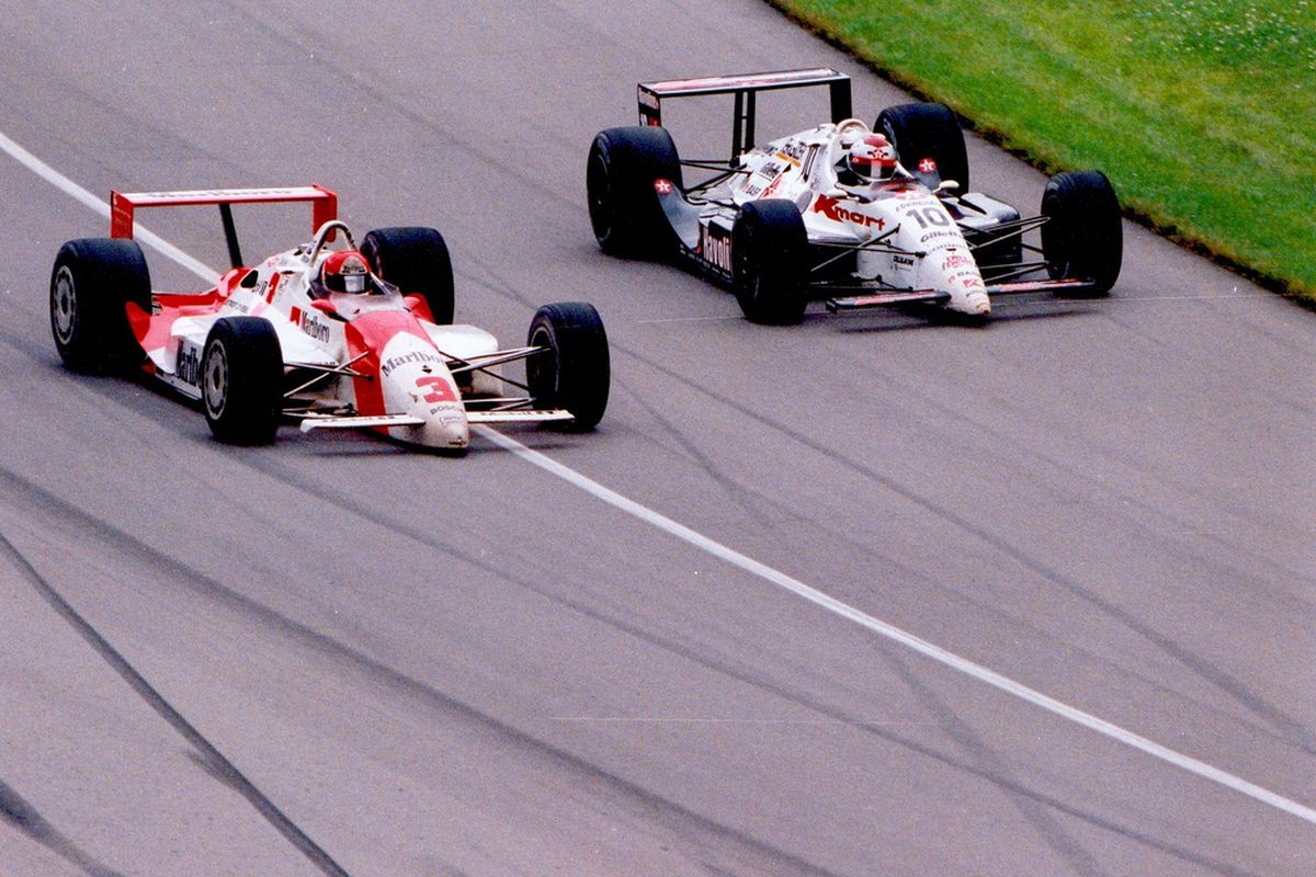 Michael Andretti (R) passes Rick Mears (L) on the apron at the Indianapolis Motor Speedway during the 1991 Indianapolis 500 (Photo: IMS)