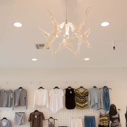 Samples hang on the walls alongside a chandelier made of hangers, yes hangers.