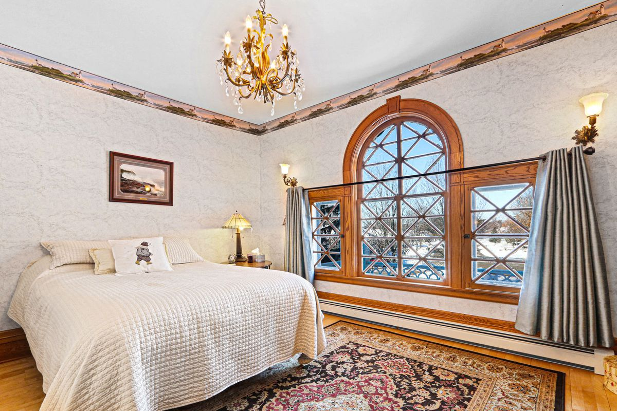 A bedroom with cream bed, rug, chandelier, and wood-trimmed windows.