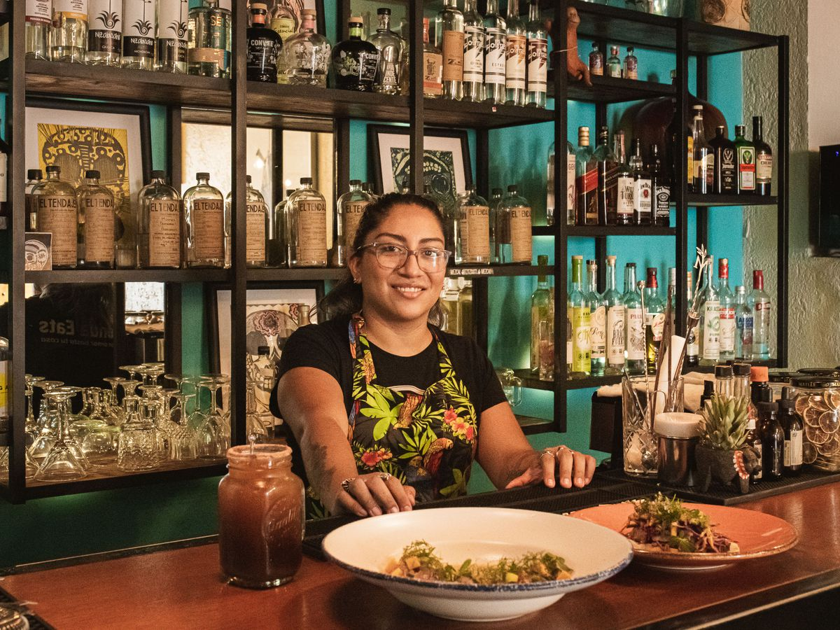 A woman smiles from behind a bar where two dishes of food sit.