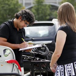 In this Sept. 9, 2011, photo, Mellissa Brown, right, a volunteer for Organizing for America, collects a signature from Jay Gupta for a petition in Columbus, Ohio, in a ballot repeal effort by opponents of the Ohio's new elections law. After years of expanding when and how people can vote, state legislatures now under new Republican control are moving to trim early voting days, beef up identification requirements and put new restrictions on how voters are notified about absentee ballots.