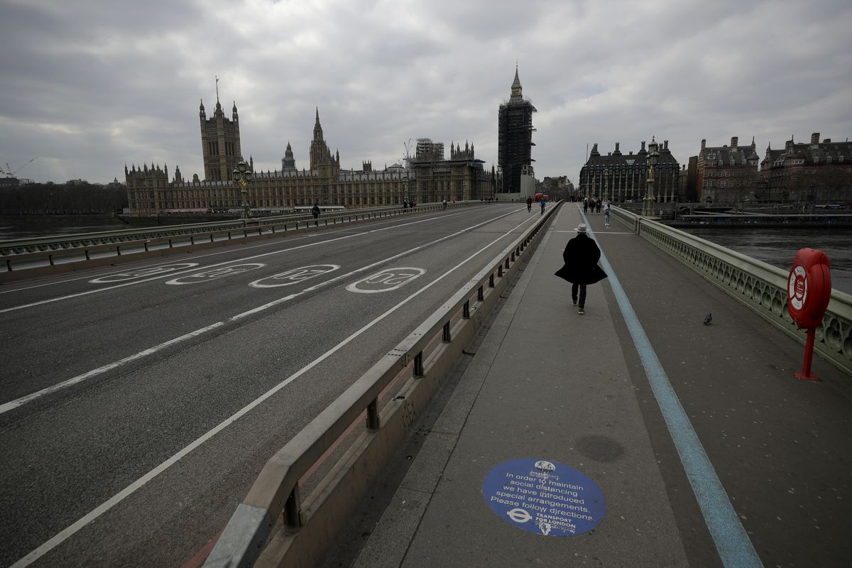People cross over a quiet Westminster Bridge, backdropped by the scaffolded Houses of Parliament and the Elizabeth Tower, known as Big Ben, in London, during England's third coronavirus lockdown.