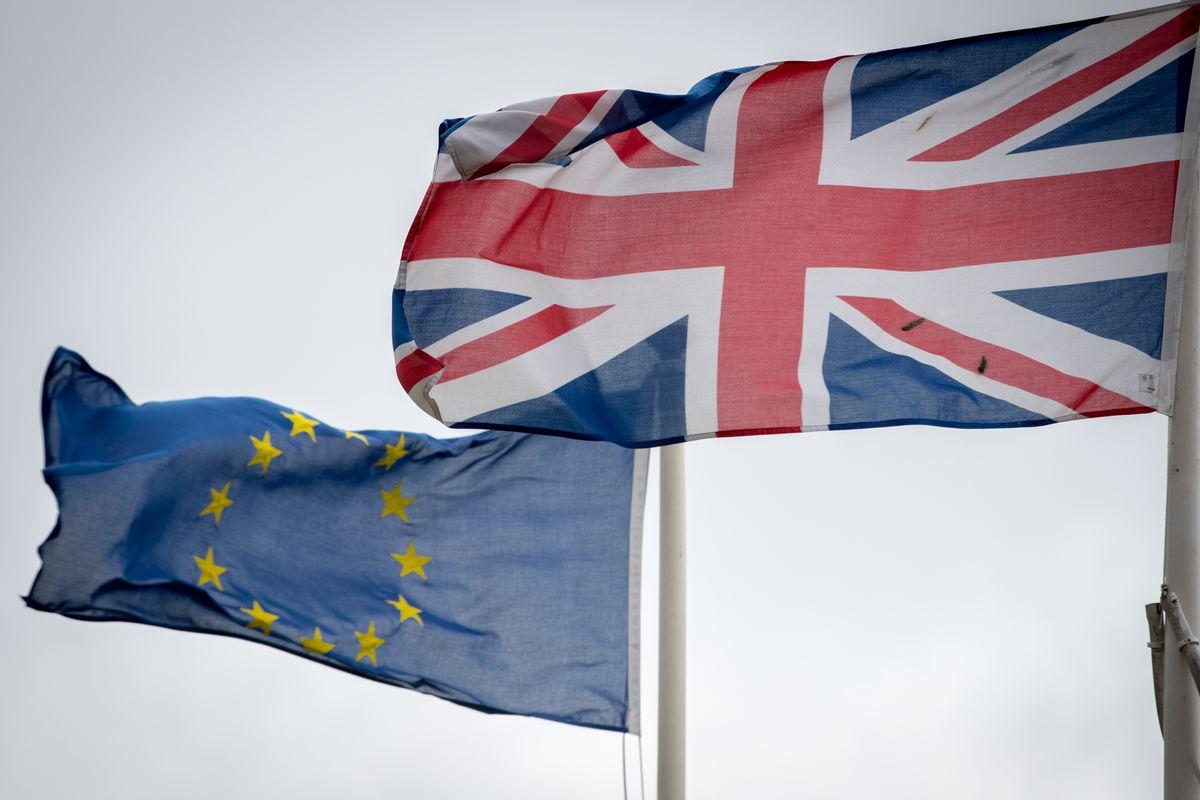 A European Union flag flying beside a United Kingdom flag.