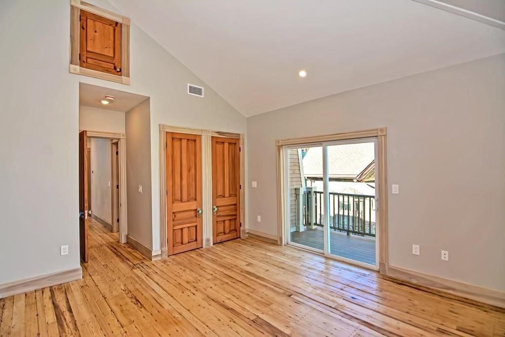 An empty room with a peaked ceiling and a sliding glass door to a deck.