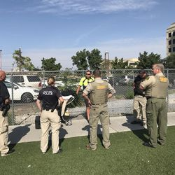 Rep. Paul Ray, R-Clearfield, center with back to the camera, wears a bulletproof vest as he walked with other law enforcers around the Rio Grande area on Monday, Aug. 14, 2017, watching Operation Rio Grande.