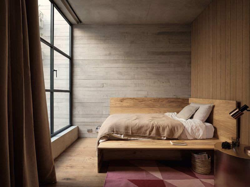 Bedroom with timber bed and large, steel-framed windows