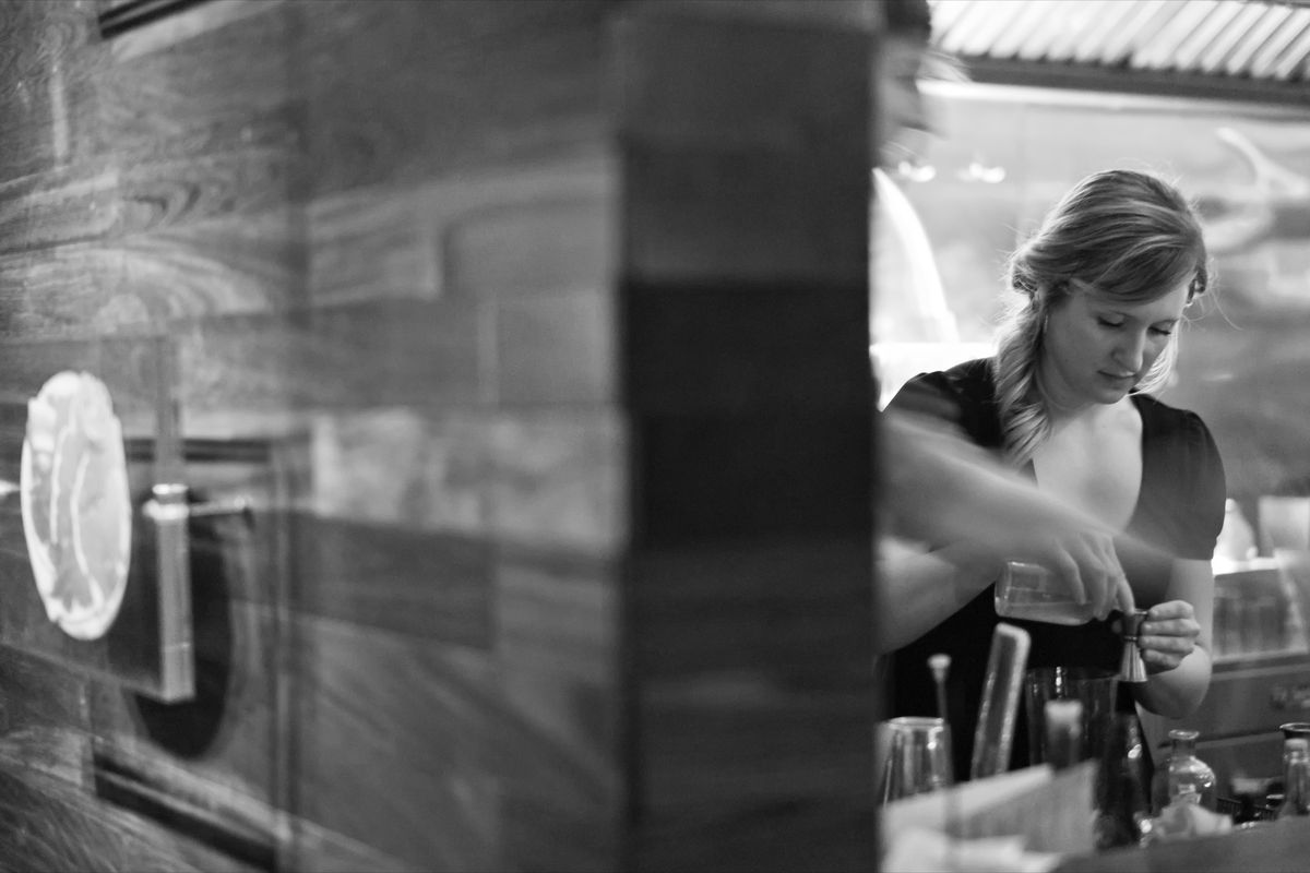 A bartender at Momofuku Ssäm Bar's Booker and Dax, in a black and white photo, makes a cocktail, pouring a liquid into a jigger