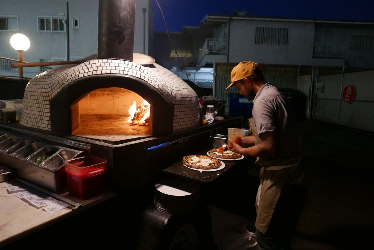 A man saucing pizza stands to the left of a white-tiled pizza oven with a fire inside