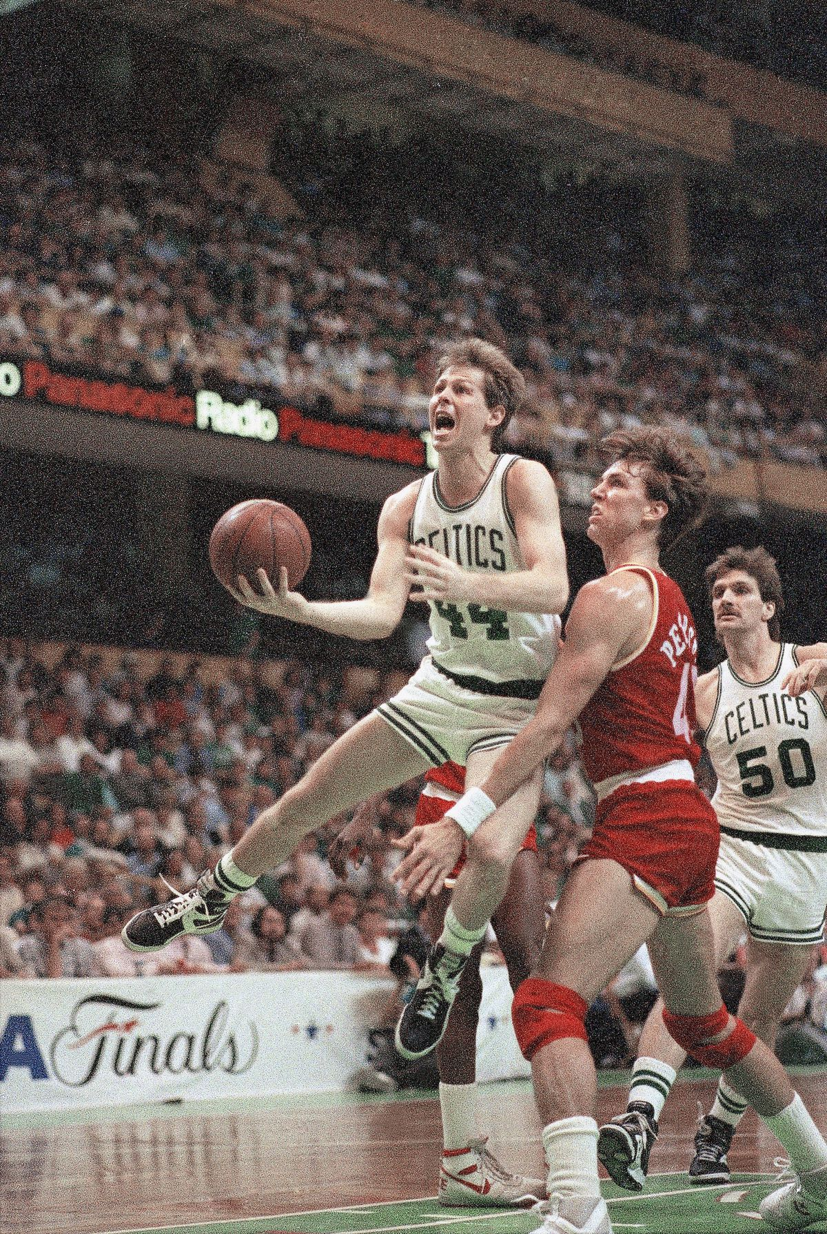 Boston's Danny Ainge (44) drives past Houston's Jim Petersen in an NBA playoff game at Boston Garden.