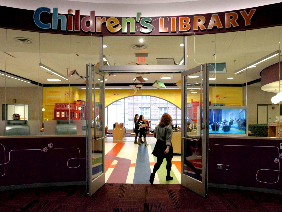 A colorful children's library entrance with people coming in and out.