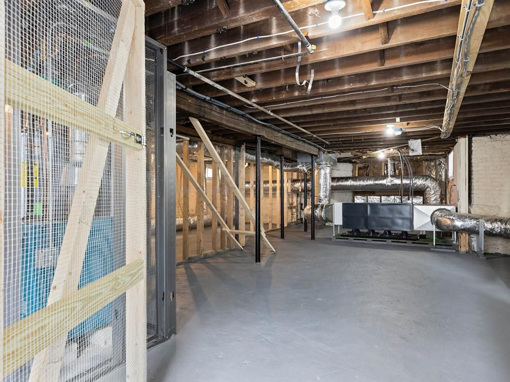 An empty basement area with exposed beams and ducts.