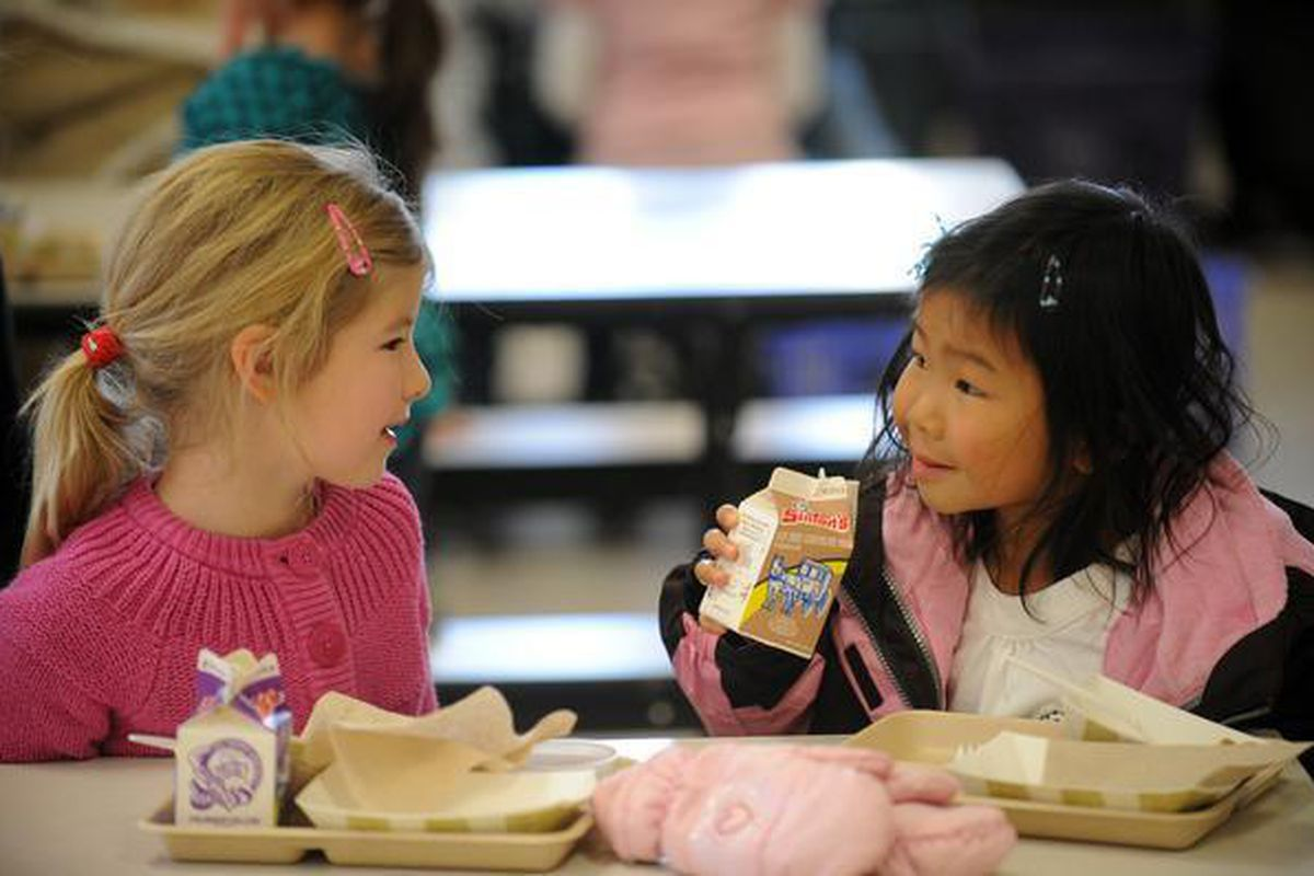 Six-year-olds Lilly Clark, left, and Zoe Burger talk during lunch at Lincoln Elementary School in Denver.
