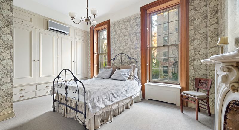 A bedroom with a small bed, two large windows, and a floral wallpaper.